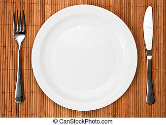 Dinner place setting - Knife, white plate and fork on bamboo...