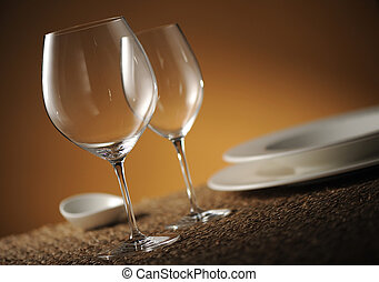 Dinner place setting with plates, glasses and cutlery shallow dof