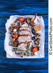 Dinner set of baked cold-boiled pork meat, fried mushrooms, baked garlic and cherry tomato. Overhead.