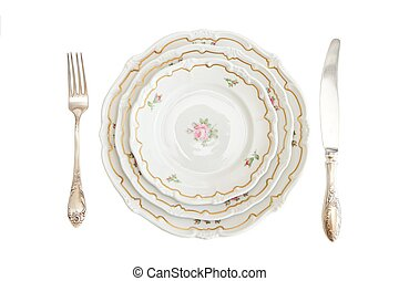 Dinner set with three plates, knife and fork isolated -...
