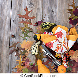 Dinner setting for autumn season with gourd decorations and leaves on rustic wooden boards