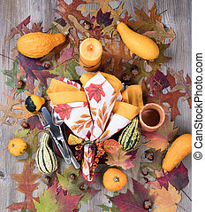 Dinner setting for fall season with burning candle plus real gourd decorations and leaves on rustic wooden boards