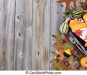 Dinner setting for fall season with gourd decorations and leaves on rustic wooden boards