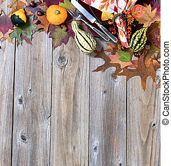 Dinner setting for fall season with real gourd decorations and leaves on rustic wooden boards