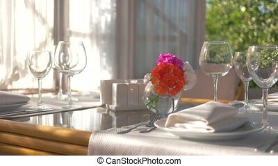 Dinner table, vase with flowers. Empty glasses on white...