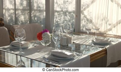 Dinner table with dishware. Plates, napkins and wineglasses.