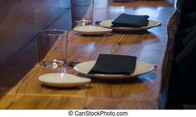 Vertical dolly shot of wooden bar counter - Dinner. Vertical...