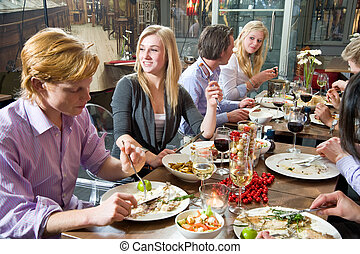 Dinnertime - Group of people enjoying a rich dinner in a ...