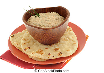 Spinich dip served in a wooden bowl with flatbread.