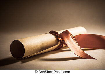 A parchment diploma scroll, rolled up with red ribbon laid at an oblique angle. Processed to give a vintage or retro appearance.