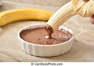 Dipping a banana in chocolate sauce