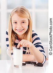 Dipping a cookie. Cute little girl dipping cookie in milk and smiling