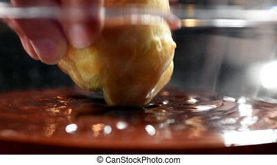 Dipping Cream Puff in Chocolate Ganache Close Up