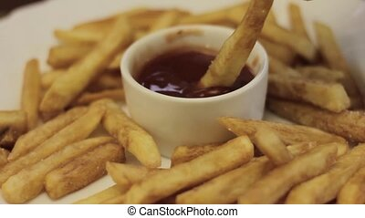 Dipping french fry into small cup of ketchup. Close-up