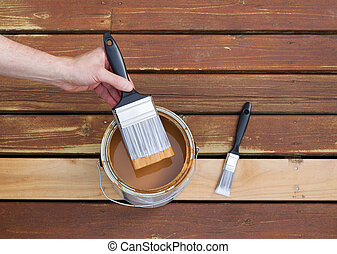 Dipping paint brush into a can of wood stain - Horizontal...