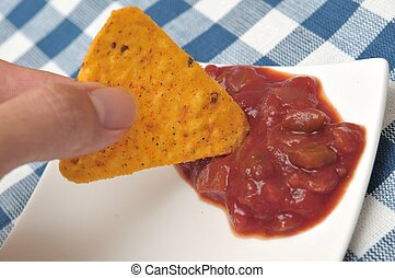 Dipping tortilla chip into sauce - Dipping single tortilla...