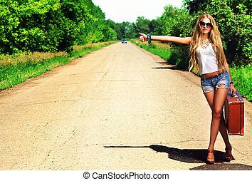 direction - Pretty young woman hitchhiking along a road.