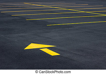 Parking lot with yellow directional arrow