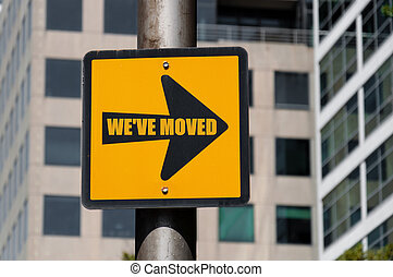 Directional sign with conceptual message WE HAVE MOVED