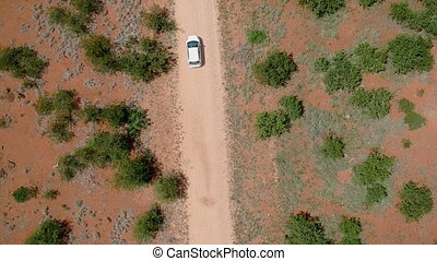 Car driving on South African African savannah road. Overhead shot. Aerial view.