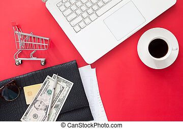 Directly above of workspace with laptop computer, money and credit card on red color background