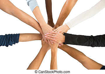 Directly above shot of creative business team piling hands against white background