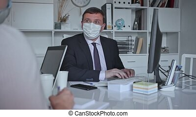 Director and secretary in protective medical masks work in the office
