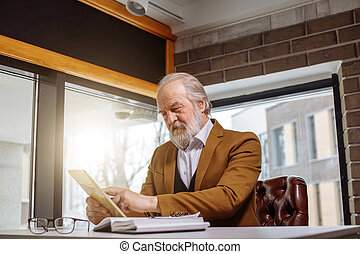 director in stylish orange suit looking at screen of the tablet