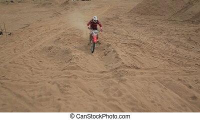 Dirt bike off roading on sand dune, aerial shot