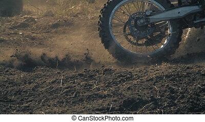Motocross bikers skidding on the dirt road
