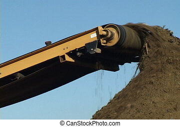 Dirt On Conveyer - Dirt moves along a conveyer belt dropping...