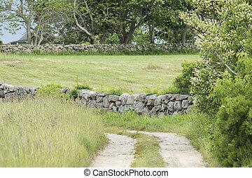 Dirt road along stone wall