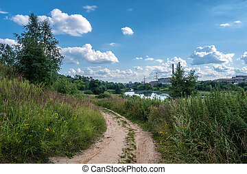 Dirt road along the Uvod river on a sunny summer day.