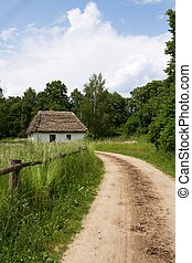 dirt road and a small house