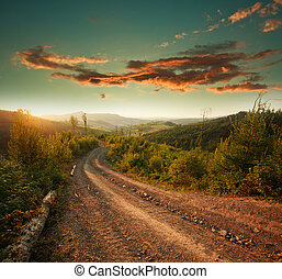 Dirt road in mountains at sunset dramatic sky background