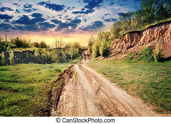 Dirt road passing by earthen cliff to the sun
