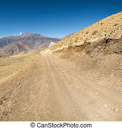 Dirt road through arid mountain wastelands.
