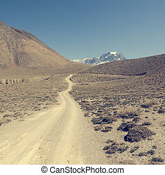 Dirt road through arid mountain wastelands.