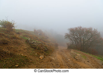 Dirt road to the mountain, autumn landscape of mountains in dense fog