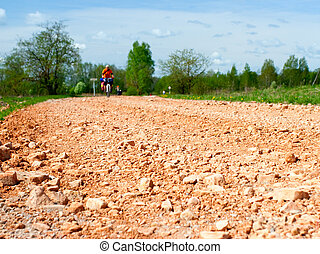 Dirt road - Traveling cyclists on dirt road, focus on the...