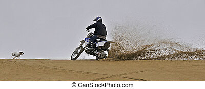 Dirtbike off roading in sand dune