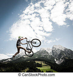 dirtbiker jumps high with his bike in front of mountains