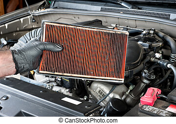 Dirty air filter - An auto mechanic wearing protective work...