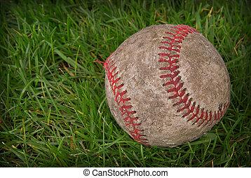 Dirty baseball in grass