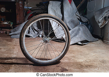 Dirty Bicycle Wheel on the Floor of a Messy Home Garage.