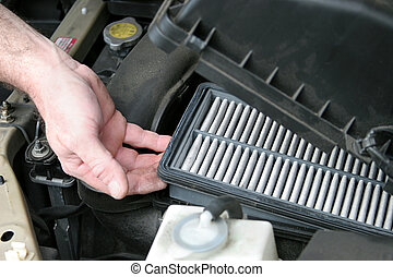 An auto mechanic removing the dirty air filter from an automobile.