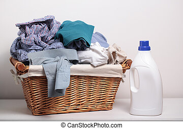 Dirty clothes in the laundry basket and a bottle of ...