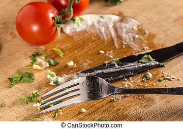 Dirty cutlery on wooden surface with cherry tomatoes