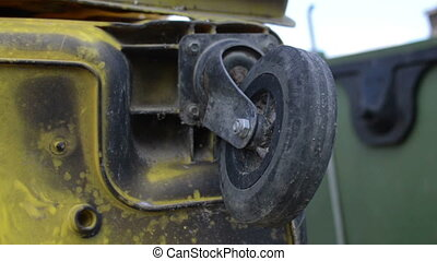Dirty damaged metal dumpsters   with broken wheel