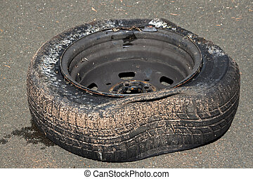 Dirty Deflated Tire on Rim Due to Blowout